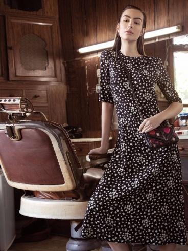 فستان من الحرير المطبع بالنجوم وحقيبة من الجلد من Saint Laurent.