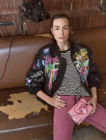 جينز باللون الوردي، وقميص قطني مخطط وسترة قصيرة مطبعة باللصائق من Marc Jacobs. حقيبة صغيرة من Jimmy Choo.
