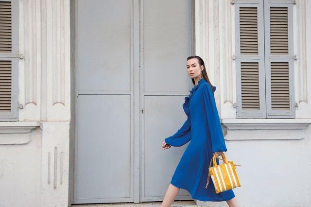 فستان من الحرير الأزرق، وحقيبة من الجلد المخطط باللونين الخردلي والأبيض، من Balenciaga.