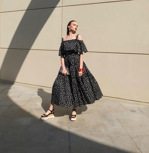 فستان قطني مطبع بالنقاط ومكشوف الكتفين، وحقيبة متناسقة، وسوار وأقراط للأذنين. الكل من Dolce&Gabbana. حذاء من Stella McCartney.